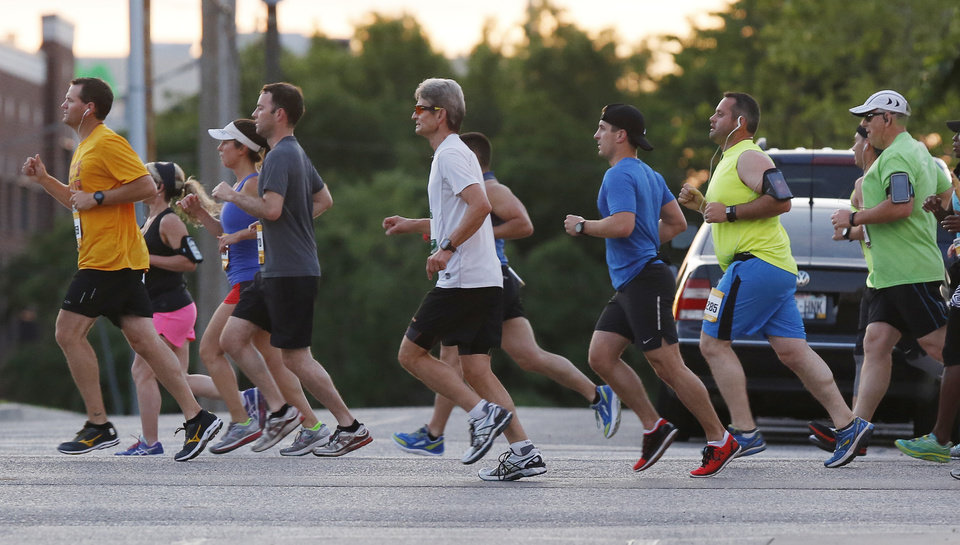 Photo - Runners travel north on Walnut Ave. after crossing the Dr. G.E. Finley Bridge during the Oklahoma City Memorial Marathon in Oklahoma City, Sunday, April 24, 2016. Photo by Nate Billings, The Oklahoman