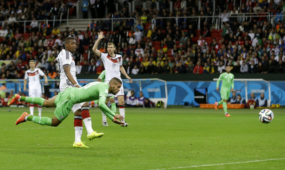 Photo - Algeria's Islam Slimani is airborne in front of Germany's Jerome Boateng after heading the ball at Germany's goal during the World Cup round of 16 soccer match between Germany and Algeria at the Estadio Beira-Rio in Porto Alegre, Brazil, Monday, June 30, 2014.  (AP Photo/Kirsty Wigglesworth)