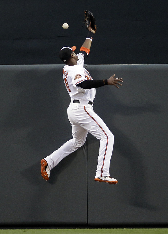 Photo -   Baltimore Orioles center fielder Adam Jones leaps but can't catch a two-run home run by Texas Rangers' Josh Hamilton in the first inning of a baseball game in Baltimore, Tuesday, May 8, 2012. (AP Photo/Patrick Semansky)
