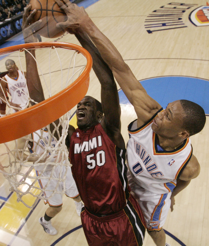 Photo - Oklahoma City Thunder guard Russell Westbrook, right, gets his hand on the ball to block a shot by Miami Heat center Joel Anthony, left, in the first quarter of an NBA basketball game in Oklahoma City, Sunday, Jan. 18, 2009. (AP Photo/Sue Ogrocki) ORG XMIT: OKSO103