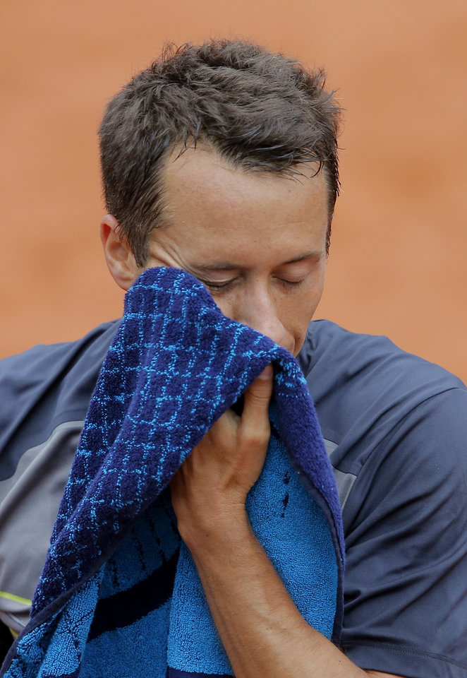 Photo - Germany's Philipp Kohlschreiber wipes his face as he plays Britain's Andy Murray during their third round match of  the French Open tennis tournament at the Roland Garros stadium, in Paris, France, Sunday, June 1, 2014. Murray won 3-6, 6-3, 6-3, 4-6, 12-10. (AP Photo/Michel Spingler)