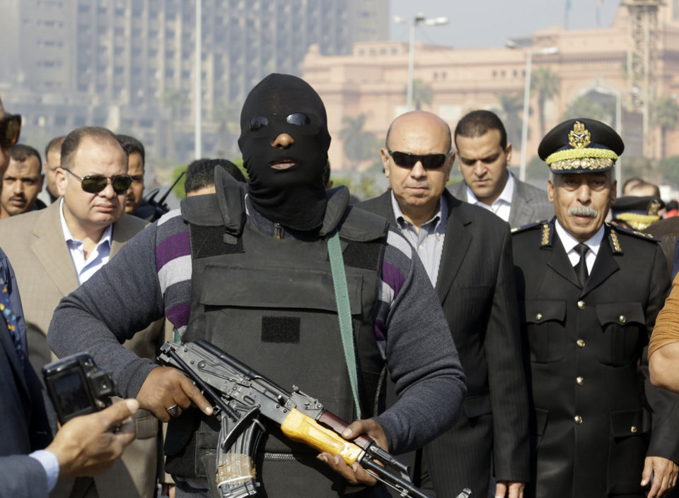 Photo - An Egyptian masked policeman guards Cairo's state security chief, Osama al-Saghir, third right, as he visits Tahrir Square, the epicenter of the 2011 uprising, in Cairo, Egypt, Saturday, Jan. 25, 2014. Demonstrators began gathering Saturday in Egypt's Tahrir Square to mark the third anniversary of the start of its 2011 revolution, though streets remained empty elsewhere in a city on edge following a spate of bombings claimed by militants. The interim government has blamed the Muslim Brotherhood group for the violence and designated it as a terrorist organization while the group denied any links to terrorism. (AP Photo/Amr Nabil)