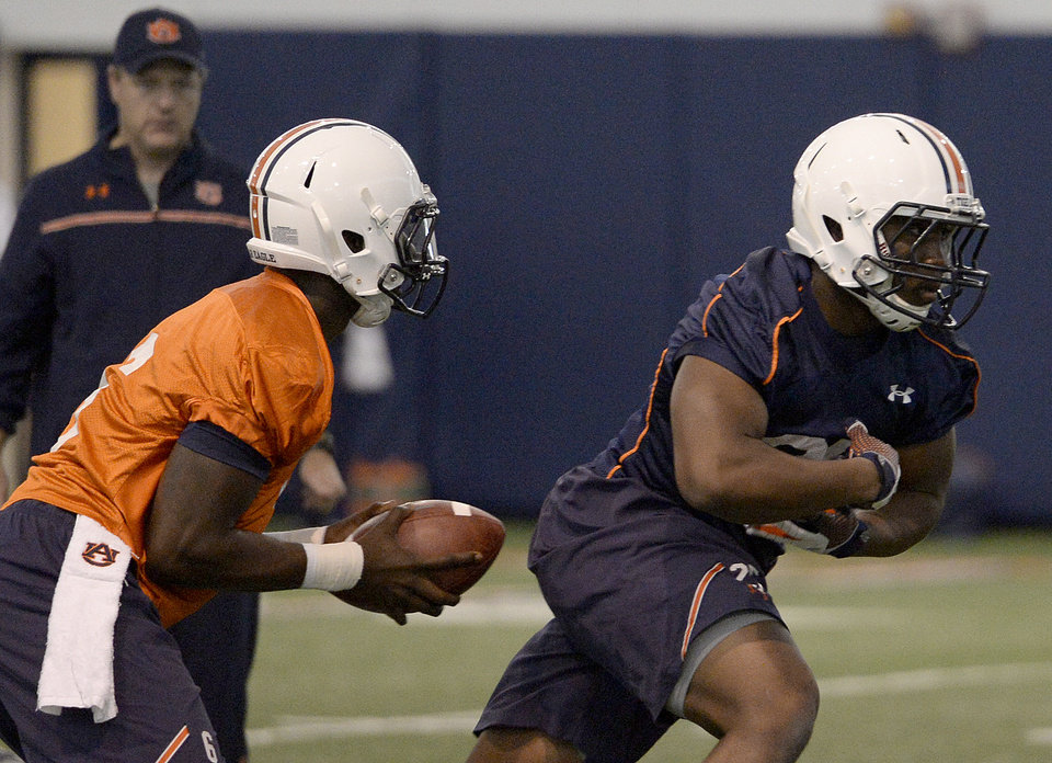 Photo - Auburn quarterback Nick Marshall (14) fakes a hand off to running back Peyton Barber (25) during Auburn's first spring practice Tuesday, March 18, 2014, at the Auburn Athletic Complex in Auburn, Ala. (AP Photo/AL.com, Julie Bennett)