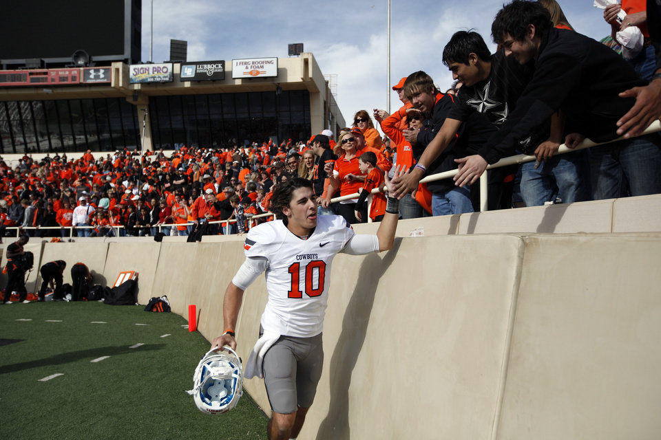 Oklahoma State\'s Clint Chelf (10) celebrates with fans following a college football game between Texas Tech University (TTU) and Oklahoma State University (OSU) at Jones AT&T Stadium in Lubbock, Texas, Saturday, Nov. 12, 2011. Photo by Sarah Phipps, The Oklahoman ORG XMIT: KOD