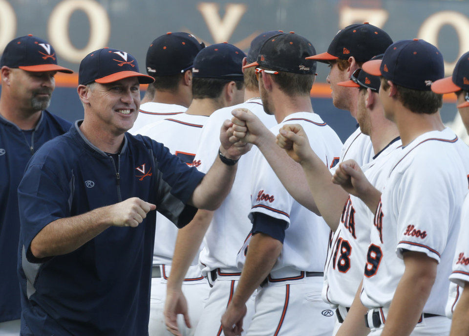 Photo - Virginia baseball coach Brian O'Connor, left, fist bumps players during introductions at an  NCAA Super Regional baseball game in Charlottesville, Va., Monday, June 9, 2014. (AP Photo/Steve Helber)