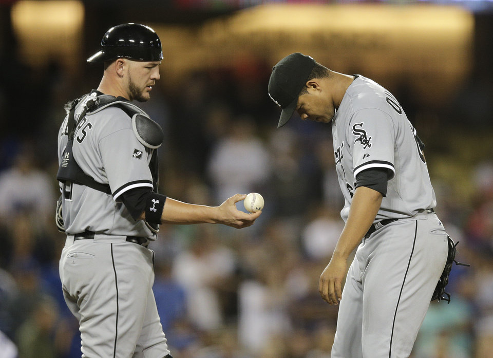 Photo - Chicago White Sox catcher Tyler Flowers, left, hands the ball to starting pitcher Jose Quintana during the sixth inning of a baseball game against the Los Angeles Dodgers on Monday, June 2, 2014, in Los Angeles. (AP Photo/Jae C. Hong)