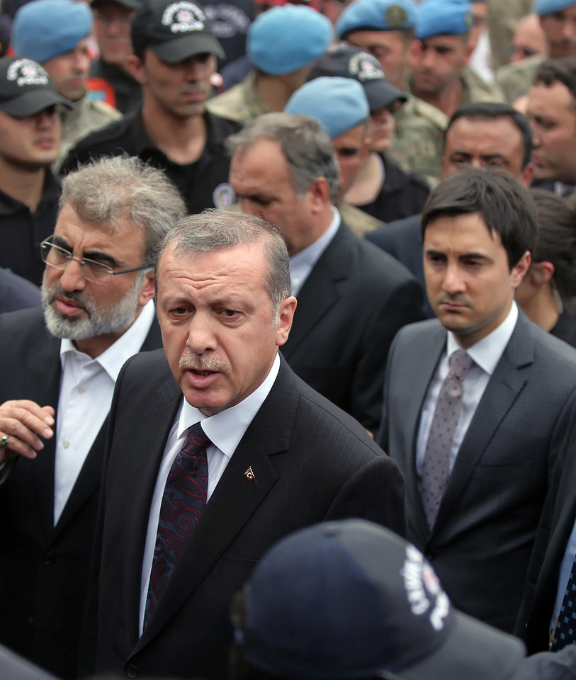 Photo - In this Wednesday, May 14, 2014 photo, Yusuf Yerkel, right, advisor to Turkish Prime Minister Recep Tayyip Erdogan, stands behind Erdogan during his visit in Soma, Turkey. Yerkel  was identified by Turkish media as the advisor who kicked a protester who was held by special forces police members during Erdogan's visit to  Soma, Turkey. Erdogan was visiting the western Turkish mining town of Soma after Turkey's worst mining accident . (AP Photo/Emrah Gurel)