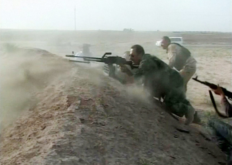 Photo - This image made from video shows Kurdish Peshmerga security forces fighting militants from the al-Qaida inspired Islamic State of Iraq and the Levant (ISIL) in Tel Al Wared, 20 kilometers west of Kirkuk, Iraq on Saturday, June 14, 2014. After a decades-long dispute between Arabs and Kurds over the oil-rich northern Iraqi city of Kirkuk, it took just an hour and a half for its fate to be decided. As al-Qaida-inspired militants advanced across northern Iraq and security forces melted away, Kurdish fighters who have long dominated Kirkuk ordered Iraqi troops out and seized full control of the regional oil hub and surrounding areas, according to a mid-ranking Army officer. He said he was told to surrender his weapons and leave his base. (AP Photo via AP video)