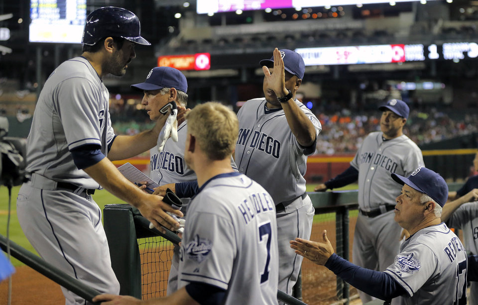 Photo - San Diego Padres' Carlos Quentin, left, is greeted in the dugout after scoring on a single by teammate Yonder Alonso during the third inning of a baseball game against the Arizona Diamondbacks, Saturday, May 25, 2013, in Phoenix.  (AP Photo/Matt York)