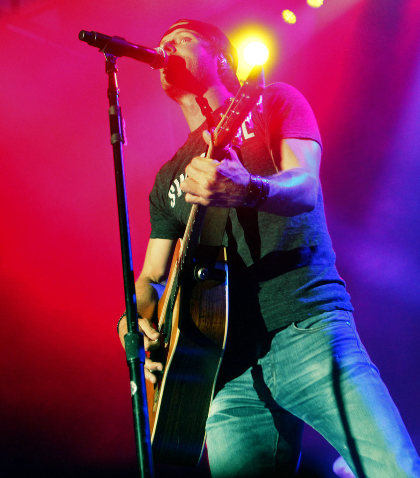 Photo - Country artist Dierks Bentley leans into the microphone as he performs the headlining set at OKC Fest in downtown Oklahoma City on Friday, June 27, 2014. OKC Fest is a new two day country music festival with multiple stages downtown. Photos by KT King/The Oklahoman