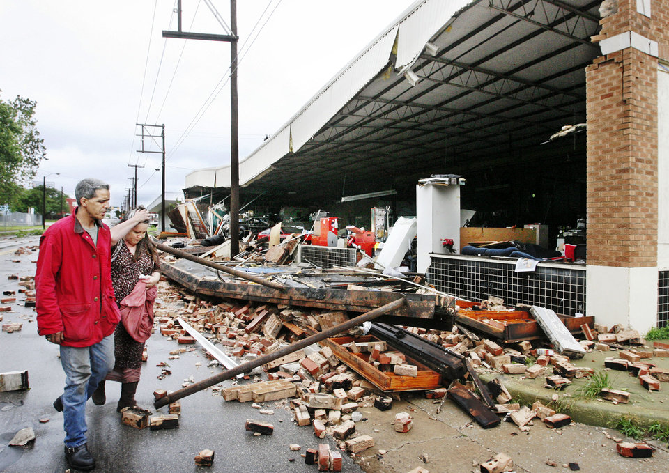 Photo - STORM AFTERMATH: Business owner Abderrahim Benqadi, left, and girlfriend, Amy Webster,  look at damage to front of his auto repair business at NW 8 and Western after heavy rains and high winds created damage in various sections of Oklahoma City Monday, May 7, 2007. Benqadi operates the business, but does not own the building. He was in the shop early Monday when high winds blew in a door on the south side of the building and then blew out the front wall on the west side of the building.    By Jim Beckel,  The Oklahoman.  ORG XMIT: KOD