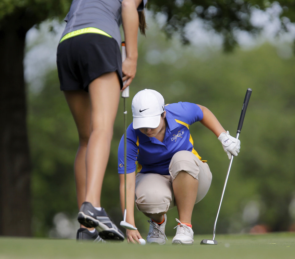 Photo - Mikera Morris of Dibble High School places her ball on the green after another golfer sunk her putt  during the 2014 Class 2A girls' golf state championship tournament  Wednesday, May 7, 2014, at Trosper Golf Course in Del City.  Photo by Jim Beckel, The Oklahoman