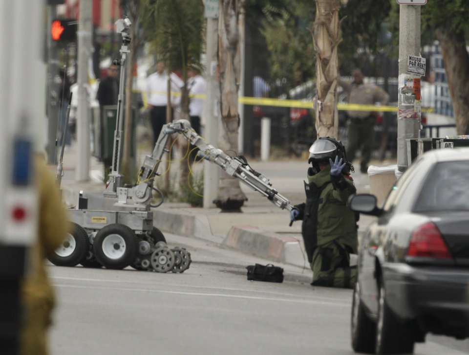 Photo -   A Los Angeles County Sheriff bomb squad member signals after rendering safe an explosive device threat outside a Bank of America branch in Los Angeles Wednesday, Sept. 5, 2012. Authorities say two gunmen kidnapped a bank manager, held her overnight and strapped a device to her stomach before robbing a Bank of America. The woman was told by the robbers the device was an explosive. The woman then had employees take money from the bank and put it outside. The suspects remain at large (AP Photo/Damian Dovarganes)