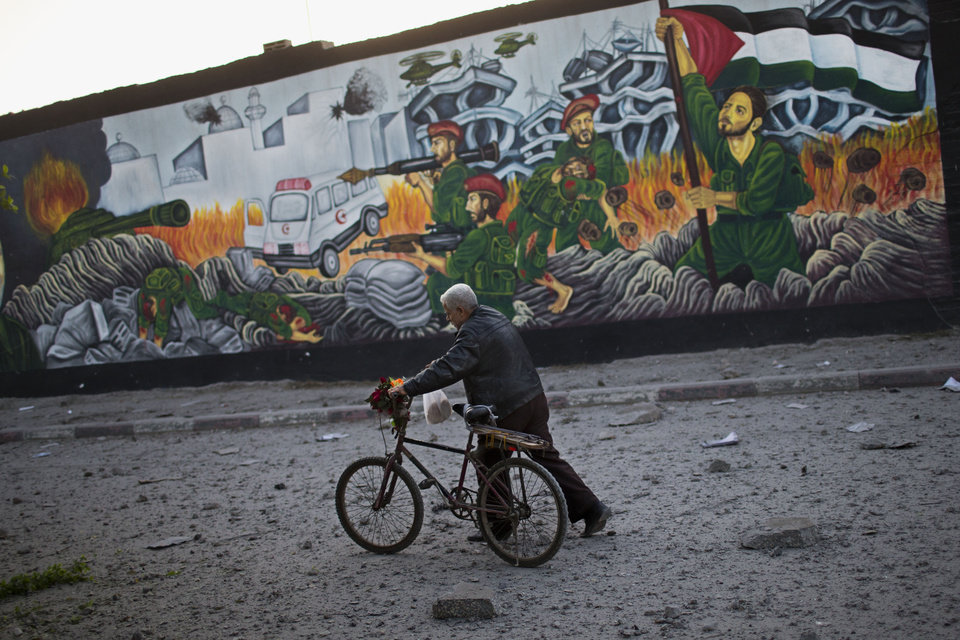 Photo -   A Palestinian man walks past a graffiti depicting Palestinian soldiers, right, figthing against Israeli soldiers moments after an Israeli forces strike in Gaza City, Sunday, Nov. 18, 2012. The Israeli military widened its range of targets in the Gaza Strip on Sunday to include the media operations of the Palestinian territory's Hamas rulers, sending its aircraft to attack two buildings used by both Hamas and foreign media outlets. (AP Photo/Bernat Armangue)