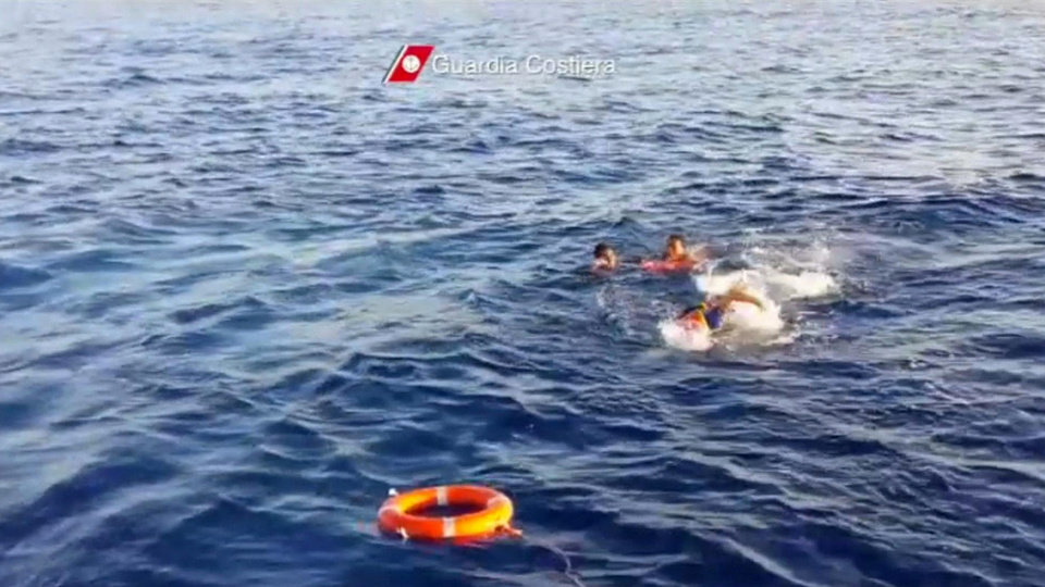 Photo - In this image made from video provided by the Italian Coast Guard and recorded on Thursday, Oct. 3, 2013, a rescuer jumps into the water to retrieve survivors of a ship transporting hundreds of migrants which caught fire and sank off the Sicilian island of Lampedusa, Italy. Authorities on Friday, Oct. 4 are contending with choppy waters in the search for dozens of migrants believed to have drowned after their rickety boat caught fire and sank off the coast of the southern Italian island of Lampedusa. (AP Photo/Italian Coast Guard)