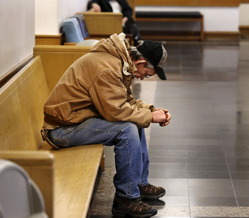Photo - A man waits on a bench in a hallway at  Workers Compensation Court in the Denver Davison Building near the state Capitol on Thursday,  Feb. 21, 2013.   Photo by Jim Beckel, The Oklahoman