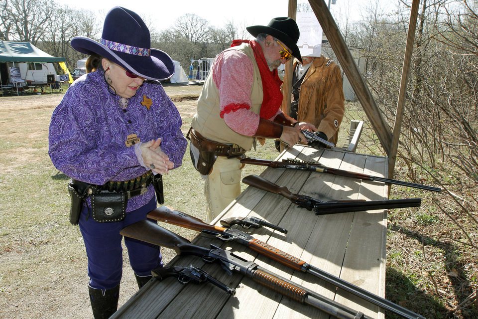 """Idaho Sue"", aka Susan Loflin, from Houston, TX, warms her hands at the loading table before starting her competition during the Land Run, the biggest cowboy action shoot of the year Friday at the Oklahoma City Gun Club. Photo By Paul Hellstern, The Oklahoman"