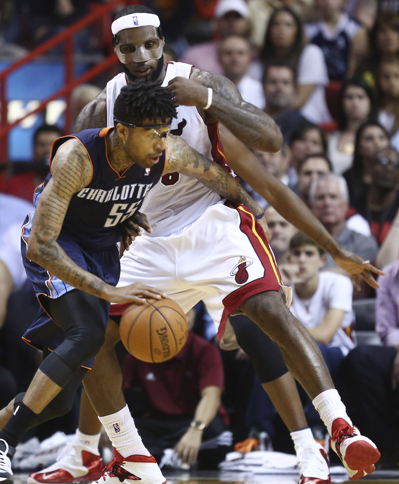 Photo - Miami Heat's LeBron James (6) blocks Charlotte Bobcats' Chris Douglas-Robert (55) during the second half of an NBA basketball game in Miami, Monday, March 3, 2014. LeBron James scored a team recond of 61 points. The Heat won 124-107. (AP Photo/J Pat Carter)