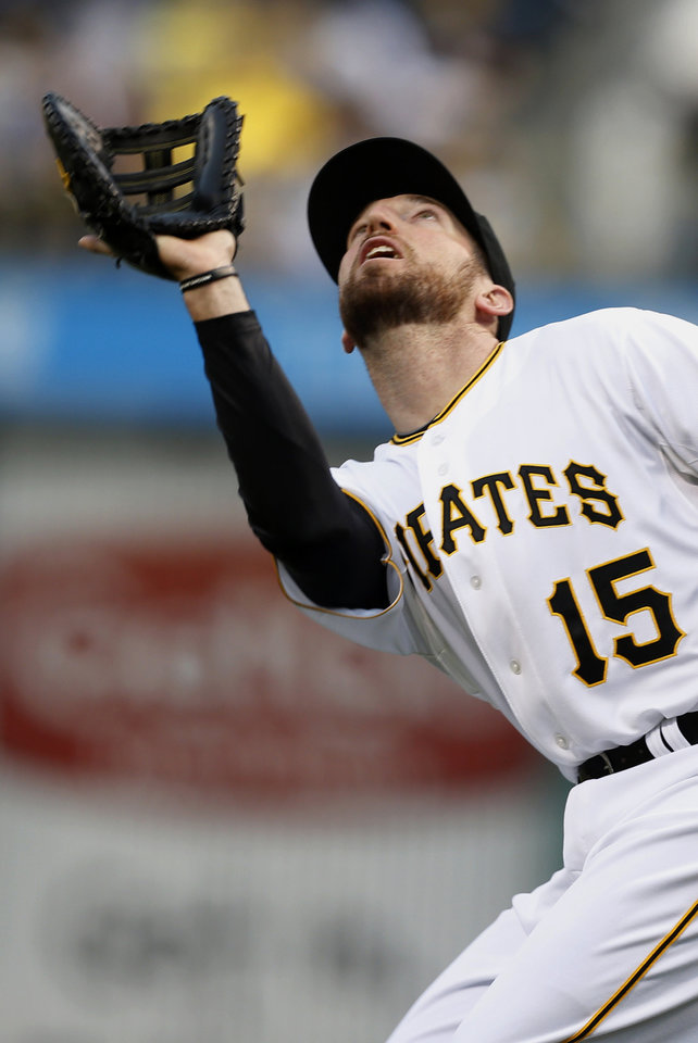 Photo - Pittsburgh Pirates first baseman Ike Davis, who was acquired from the New York Mets in a trade Friday, makes a catch of a pop fly by Milwaukee Brewers' Mark Reynolds in the second inning of the baseball game Saturday, April 19, 2014, in Pittsburgh. (AP Photo/Keith Srakocic)