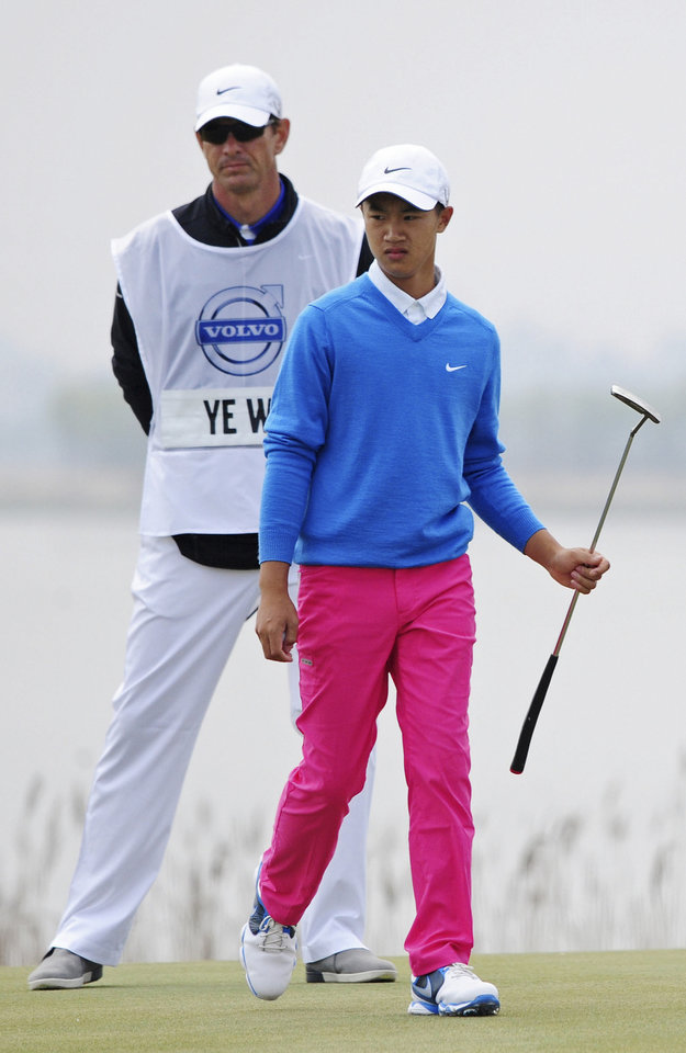 Photo - 12-year-old Chinese amateur golfer Ye Wocheng, right, with his caddy watch his putt on the second day of the Volvo China Open at the Tianjin Binhai Lake Golf Club in north China's Tianjin Municipality Friday, May 3, 2013. Ye became the youngest player ever to compete in a European Tour event. (AP Photo) CHINA OUT