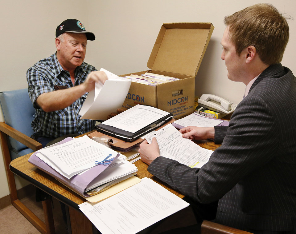 Photo - Claimant Fred Krueger, left, meets with his attorney, Alex Forbes, to review forms and statements before being called to appear in front of a judge at Workers' Compensation Court. Photos by Jim Beckel, The Oklahoman