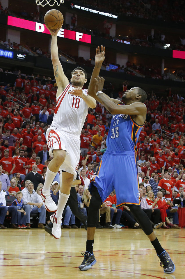 Photo - Houston's Carlos Delfino (10) goes past Oklahoma City's Kevin Durant (35) for a dunk during Game 4 in the first round of the NBA playoffs between the Oklahoma City Thunder and the Houston Rockets at the Toyota Center in Houston, Texas,Sunday, April 29, 2013. Oklahoma City lost 105-103. Photo by Bryan Terry, The Oklahoman