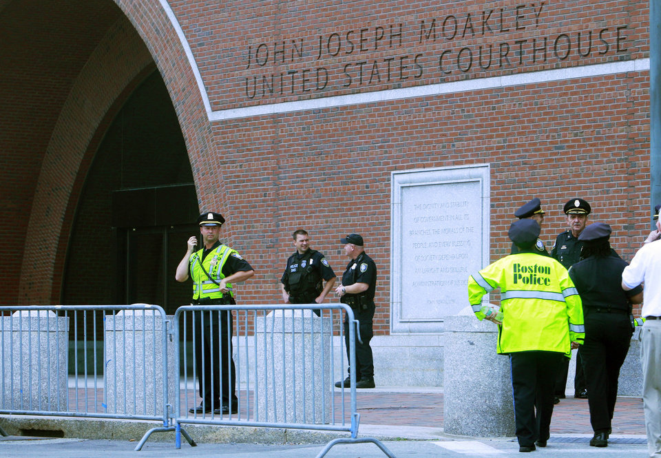Photo - Local and federal law enforcement officers stand outside the federal courthouse prior to arraignment for Boston Marathon bombing suspect Dzhokhar Tsarnaev Wednesday, July 10, 2013, in Boston. Tsarnaev is scheduled to appear in court for the first time since he was captured days after the April 15 explosion. The attack killed three and wounded more than 260. The 19-year-old Tsarnaev has been charged with using a weapon of mass destruction, and could face the death penalty. (AP Photo/Bill Sikes)