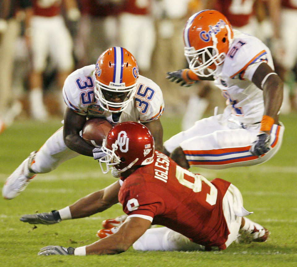 Photo - Florida's Ahmad Black (35) intercepts a Sam Bradford pass intended for OU's Juaquin Iglesias (9) next to Major Wright (21) in the fourth quarter during the BCS National Championship college football game between the University of Oklahoma Sooners (OU) and the University of Florida Gators (UF) on Thursday, Jan. 8, 2009, at Dolphin Stadium in Miami Gardens, Fla. The Florida Gators won, 24-14. PHOTO BY NATE BILLINGS, THE OKLAHOMAN