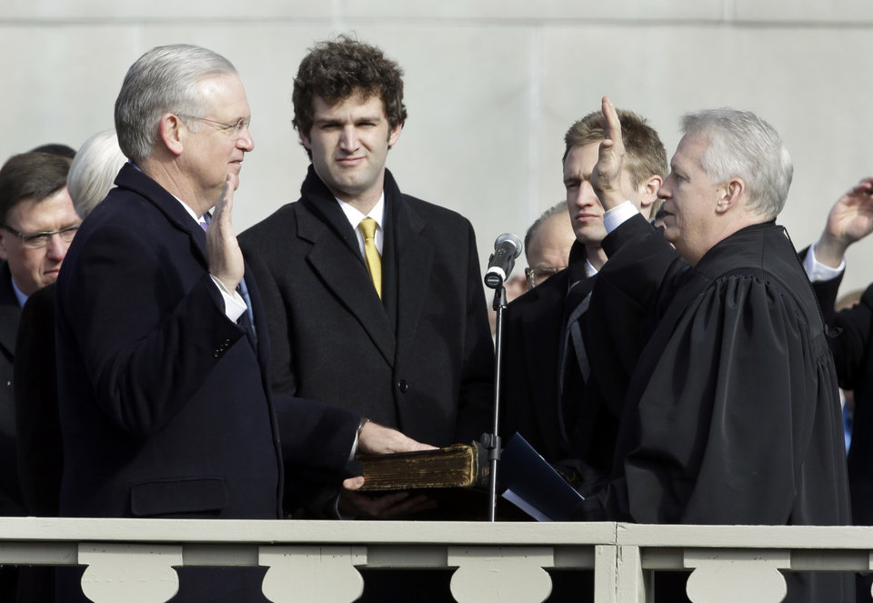 Missouri Gov. Jay Nixon, left, is sworn in to his second term by Judge Rex M. Burlison, right, while Nixon's sons Will, second from left, and Jeremiah watch Monday, Jan. 14, 2013, in Jefferson City, Mo. (AP Photo/Jeff Roberson)