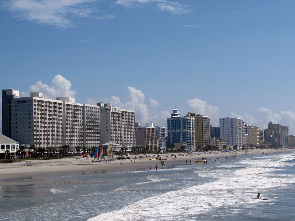 Photo - FILE - This May 22, 2013 file photo shows vacationers enjoying the beach in Myrtle Beach, S.C. Tourism is an estimated $18 billion industry in South Carolina and a new season is gearing up the week of February 9, 2014, with the Governor's Conference on Tourism and Travel on Hilton Head Island, the Southeastern Wildlife Exposition in Charleston and other events. (AP Photo/Bruce Smith, File)