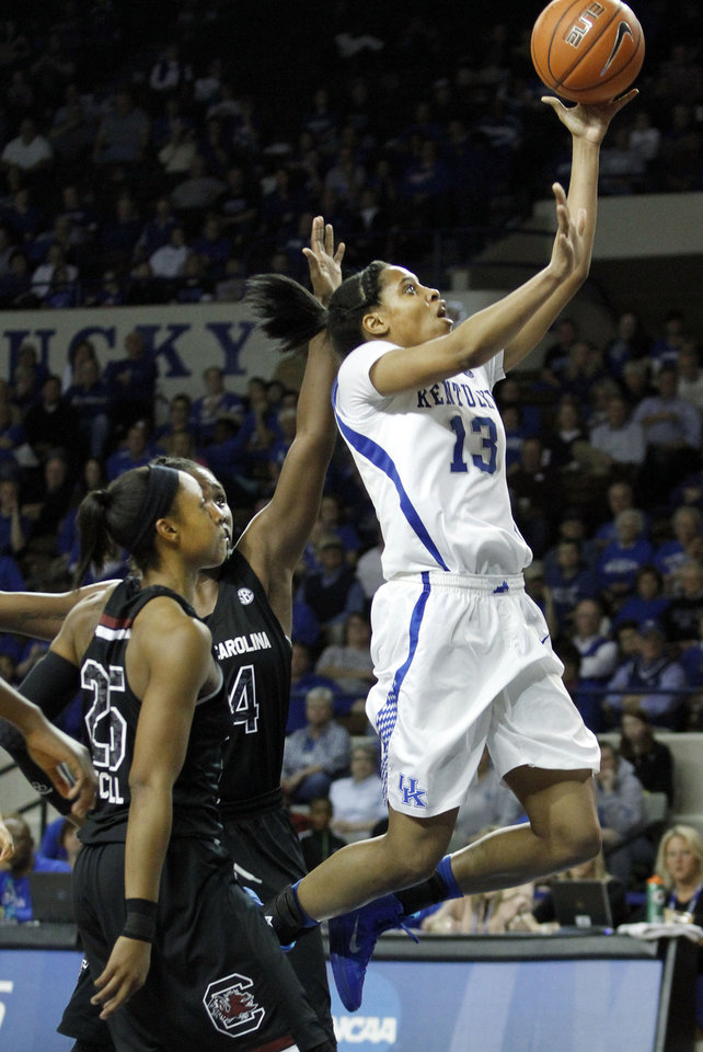 Photo - Kentucky's Bria Goss, right, shoots in front of South Carolina's Aleighsa Welch and Tiffany Mitchell, left, during the second half of an NCAA college basketball game, Thursday, Feb. 20, 2014, in Lexington, Ky. South Carolina won 81-58. (AP Photo/James Crisp)