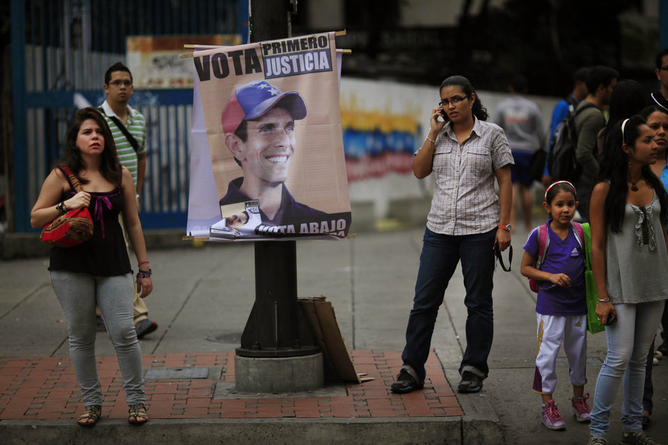 A campaign poster promoting opposition presidential candidate Henrique Capriles hangs on a pole in Caracas, Venezuela, Friday, Oct. 5, 2012. Venezuelans head to the polls Sunday to vote in their country\'s presidential election, deciding on whether to keep President Hugo Chavez or seek change with opposition candidate Henrique Capriles. (AP Photo/Ariana Cubillos)