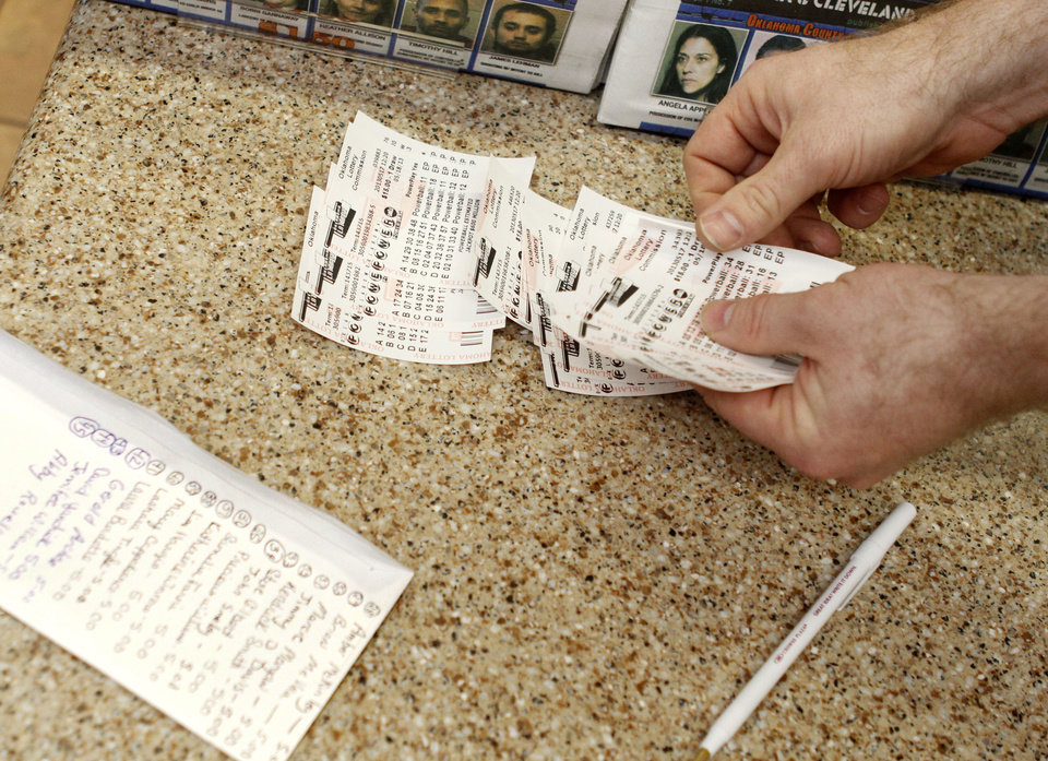 Photo - OnCue store manager David Schwarz counts out lottery tickets that were bought through an office pool Friday at the store at N 23 and Santa Fe Avenue in Oklahoma City. Photo By Paul Hellstern, The Oklahoman  PAUL HELLSTERN - Oklahoman