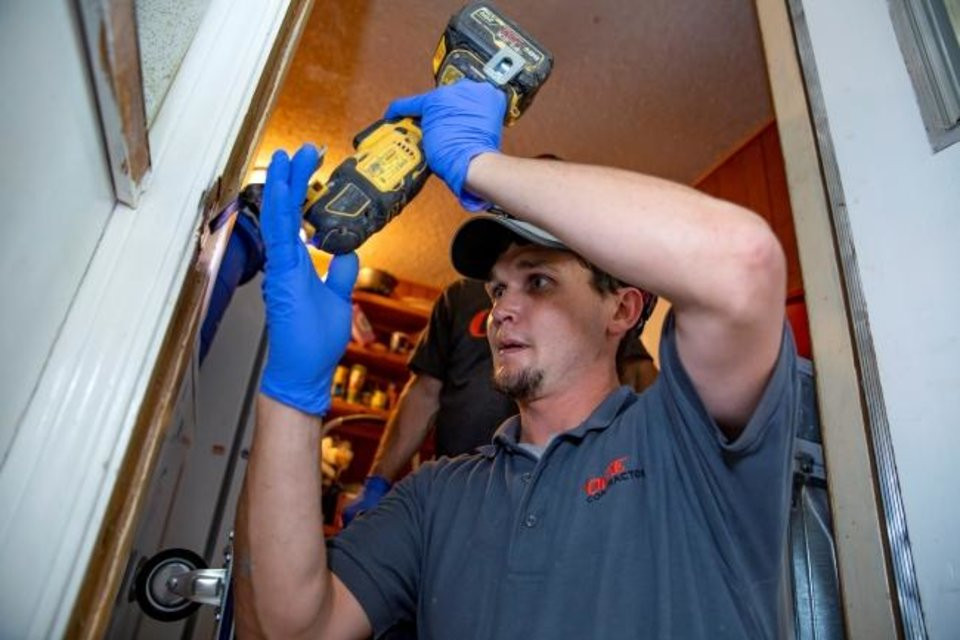 Photo -  A contractor caulks around a door during OG&E's Silver Energy Sweep initiative.