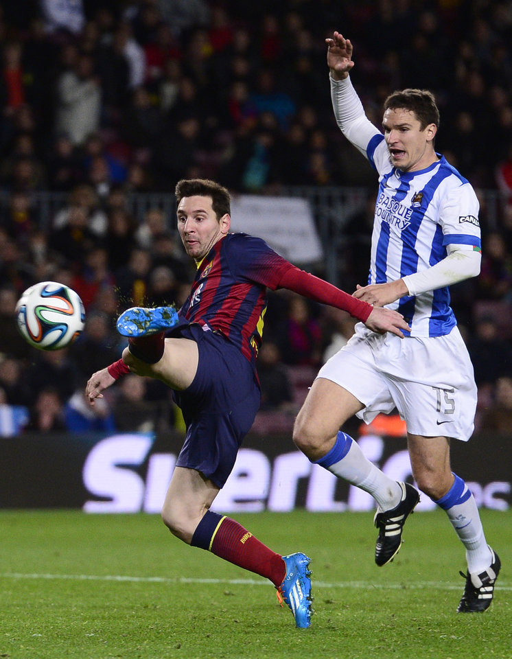 Photo - FC Barcelona's Lionel Messi, from Argentina, left, duels for the ball against Real Sociedad's Ion Ansotegi during a Copa del Rey soccer match at the Camp Nou stadium in Barcelona, Spain, Wednesday, Feb. 5, 2014. (AP Photo/Manu Fernandez)