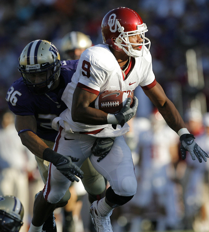 Photo - Oklahoma's Juaquin Iglesias (9) takes the ball up field past Washington's Johri Fogerson (36) in the first half during the college football game between Oklahoma and Washington at Husky Stadium in Seattle, Wash., Saturday, September 13, 2008. BY NATE BILLINGS, THE OKLAHOMAN