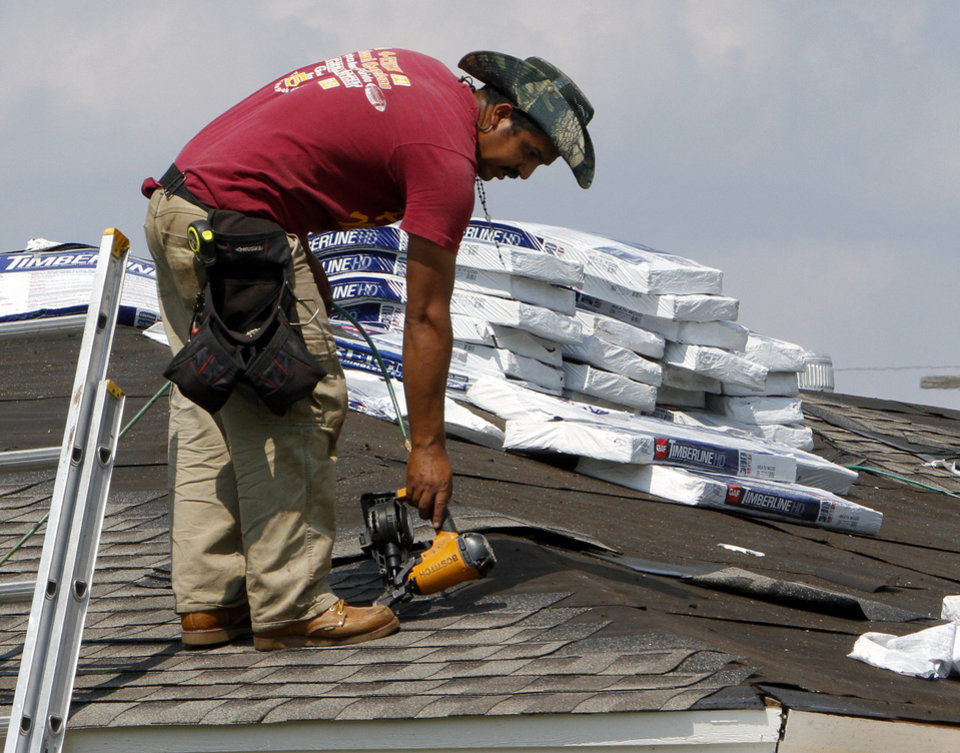 Roofers are active near the site of a tornado that damaged or destroyed homes near Telephone Road on Tuesday in Moore.  Photo by Steve Sisney, The Oklahoman <strong>STEVE SISNEY</strong>