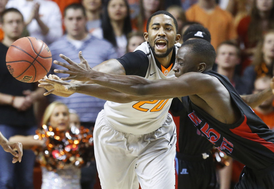 Photo - Oklahoma State's Michael Cobbins, left,  and Delaware State's Ashwell Boyd, right,  reach for a loose ball in the first half of an NCAA college basketball game in Stillwater, Okla., Tuesday, Dec. 17, 2013. (AP Photo/Sue Ogrocki)
