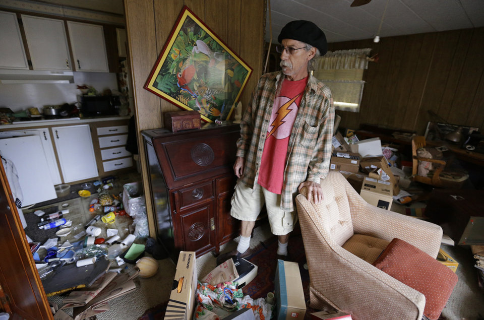 Photo - Steve Brody inspects damage to the interior of his mobile home after an earthquake Sunday, Aug. 24, 2014, at the Napa Valley Mobile Home Park, in Napa, Calif. A large earthquake caused significant damage and left at least three critically injured in California's northern Bay Area early Sunday, igniting fires, sending at least 87 people to a hospital, knocking out power to tens of thousands and sending residents running out of their homes in the darkness. (AP Photo/Ben Margot)