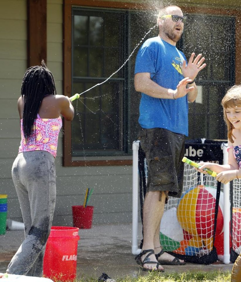 Photo -  Camp director Kyle Cottrell is hit by Angel Yeboah, 12, as they play water games at Camp ClapHans, an outreach program of the J.D. McCarty Center in Norman. PHOTO BY STEVE SISNEY, THE OKLAHOMAN   STEVE SISNEY -