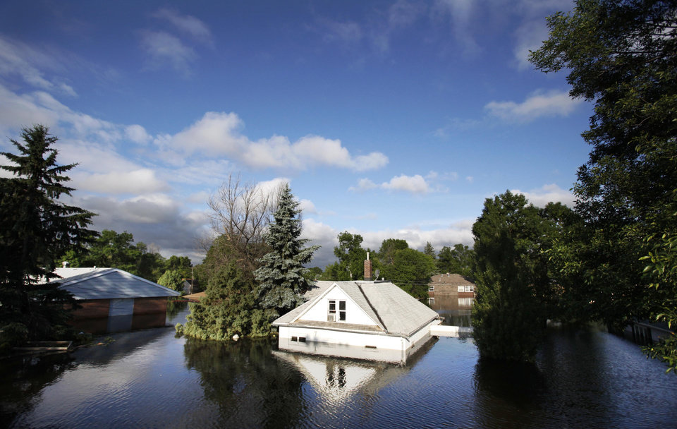 Photo - FILE - In this June 27, 2011 file photo, floodwaters from the Souris River surround homes near Minot State University in Minot, N.D. Global warming is rapidly turning America the beautiful into America the stormy, sneezy and dangerous, according to the National Climate Assessment report released Tuesday, May 6, 2014. (AP Photo/Charles Rex Arbogast)