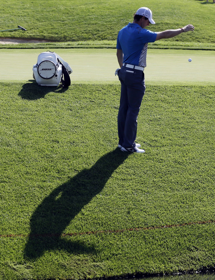 Photo - Rory McIlroy, of Northern Ireland, takes a drop after hitting into the water on the 14th hole during the second round of the Memorial golf tournament Friday, May 30, 2014, in Dublin, Ohio. (AP Photo/Darron Cummings)