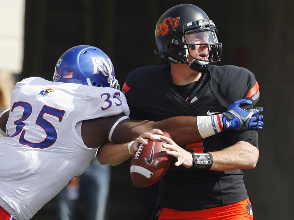 Photo - Oklahoma State's Brandon Weeden (3) is sacked by Kansas' Toben Opurum (35) during a college football game between the Oklahoma State University Cowboys (OSU) and the University of Kansas Jayhawks (KU) at Boone Pickens Stadium in Stillwater, Okla., Saturday, Oct. 8, 2011 Photo by Steve Sisney, The Oklahoman