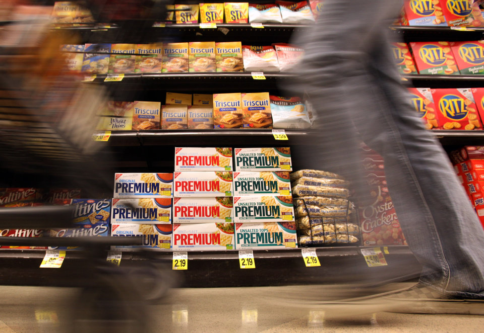Photo - FILE - In this Feb. 9, 2011 file photo, a shopper passes a shelf full of Nabisco products - Premium saltines, Triscuits, Ritz crackers and Wheat Thins - at a Ralphs Fresh Fare supermarket in Los Angeles. Nabisco is a Mondelez International brand. Mondelez International reports quarterly earnings on Wednesday, May 7, 2014. (AP Photo/Reed Saxon, File)