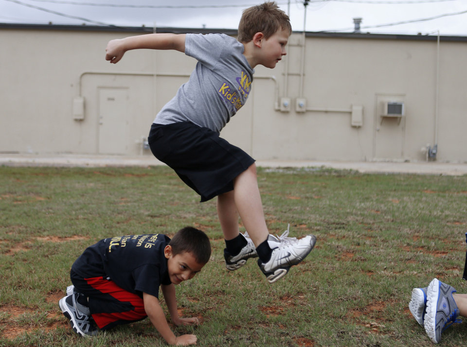 Photo - Ty Morrison, 8, leaps over Brandon Anderson, 6, during a game of leap frog at Kid's Maniac Fitness in Moore, Okla., Tuesday, April 9, 2013. Photo by Bryan Terry, The Oklahoman  Bryan Terry