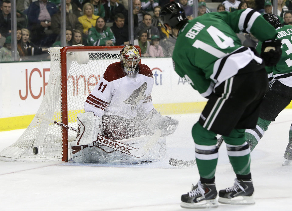 Photo - Phoenix Coyotes' Mike Smith (41) deflects a shot from Dallas Stars' Jamie Benn (14) in the first period of an NHL hockey game, Saturday, Feb. 8, 2014, in Dallas. (AP Photo/Tony Gutierrez)