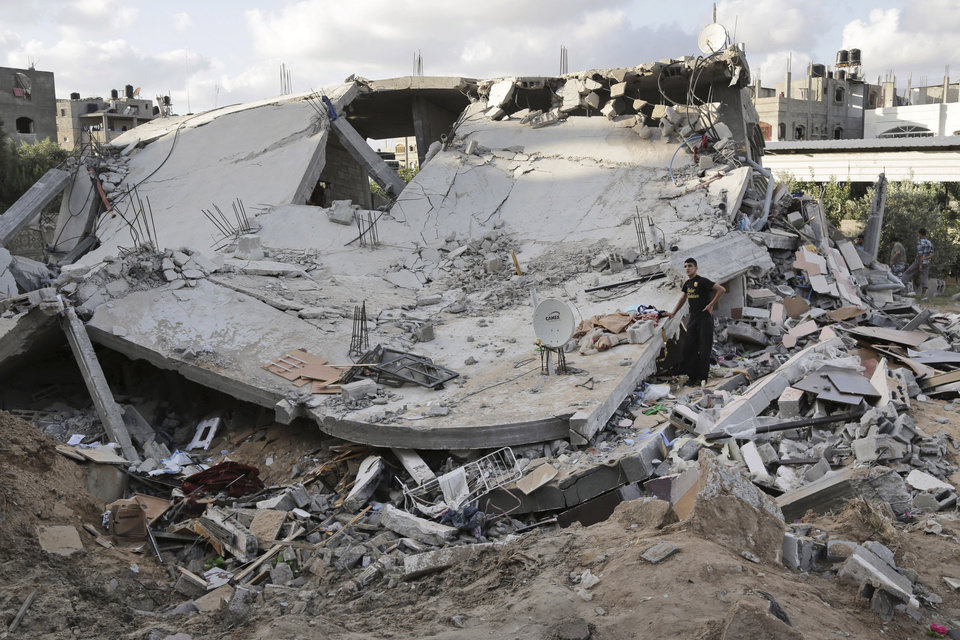 Photo - A Palestinian youth inspects a heavily damaged building after it was hit by an Israeli airstrike in Beit Lahiya, northern Gaza Strip, Tuesday, July 15, 2014. The Israeli military says it has resumed airstrikes on Gaza after Hamas militants violated a de-escalation brokered by Egypt. (AP Photo/Adel Hana)