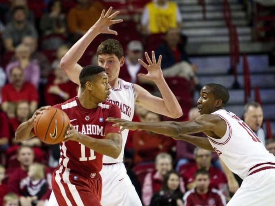 Oklahoma's Isaiah Cousins (11) looks to pass as Arkansas' BJ Young, right, and Hunter Mickelson, rear center, defend during the first half of an NCAA college basketball game in Fayetteville, Ark., Tuesday, Dec. 4, 2012. (AP Photo/Gareth Patterson)