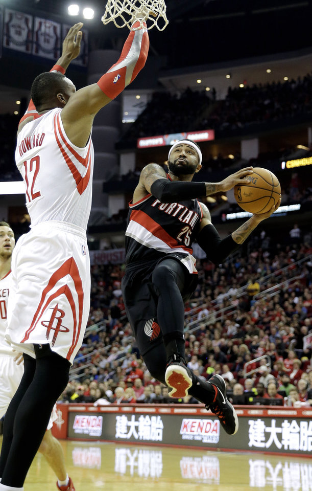 Photo - Portland Trail Blazers' Mo Williams (25) goes up to shoot as Houston Rockets' Dwight Howard (12) defends during the second quarter of an NBA basketball game on Sunday, March 9, 2014, in Houston. (AP Photo/David J. Phillip)