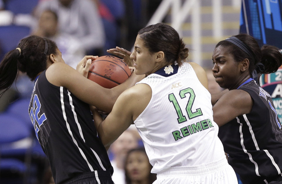Photo - Notre Dame's Taya Reimer (12) wrestles Duke's Oderah Chidom (22) and Elizabeth Williams (1) for control of a rebound during the first half of the NCAA college basketball championship game of the Atlantic Coast Conference tournament in Greensboro, N.C., Sunday, March 9, 2014. (AP Photo/Chuck Burton)